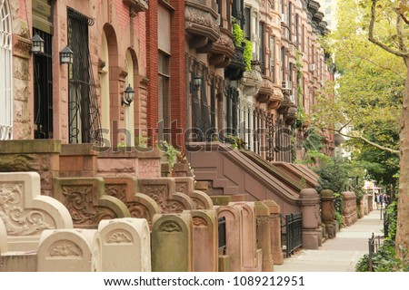 A row of various colored brownstones in uptown Manhattan, NYC