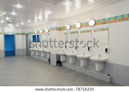 A row of washbasins with mirrors in a public toilet - stock photo
