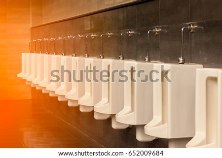 A row of white porcelain urinals.Selective focus point in public toilets with morning light. Stockfoto ©