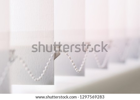 A row of white vertical blinds  cover the sunlight from the window. Close up. #1297569283