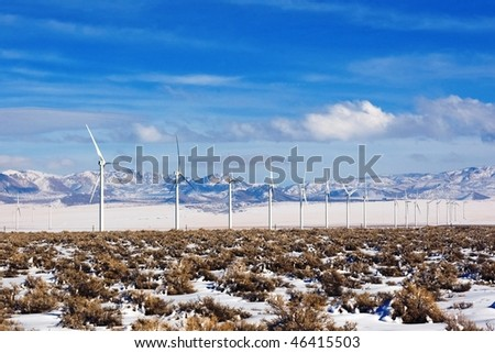 A row of wind turbines marches across a high desert area.