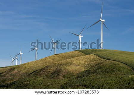 A row of wind turbines on a sunny hill