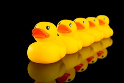 A row of yellow ducks on a black background with reflection in black table.  Concept of following the leader or lack of individuality or uniqueness