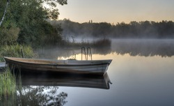 A rowboat by a pier on a calm Swedish lake with mist drifting across. It is early morning and everything is quiet.