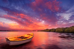 A rowboat watches an amazing sunset
