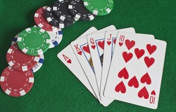 a royal flush of hearts with poker chips scattered