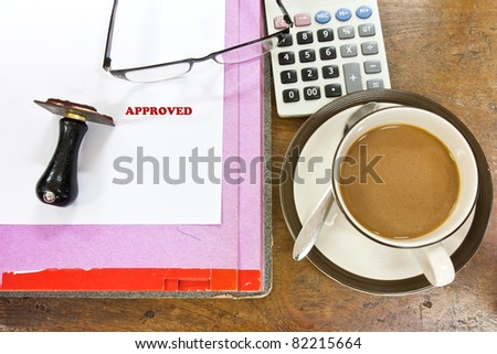A rubber stamp tool with word approved on blank white paper ,a cup of coffee ,glasses and calculator on wooden office table