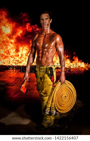 A rugged and muscular firefighter with an axe and firehose in hands and raging fire in the background. Fireman calendar.