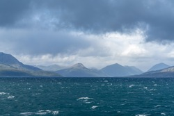 A rugged and wild coastline with mountains and stormy seas with whitecaps under and expressive cloudy sky