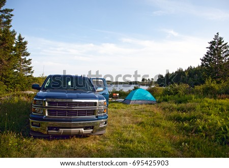 a rugged blue pickup truck is ready for a weekend adventure, with open door on a campsite and tent at a lake