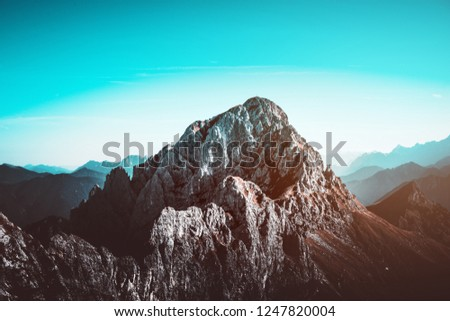 A rugged, dramatic, rocky mountain landscape and clear blue sky.