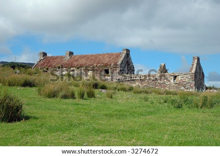 A ruin of an old Irish cottage with a green meadow on Achill Island (Ireland) on a sunny day.