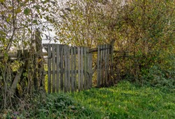 A rundown rickety wooden gate in the countryside with rays of sunshine and copy space for your text