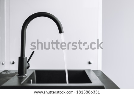 A running tap with the water running in the kitchen. The tap lets the water run, nobody.
