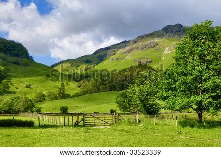 A rural landscape of green farm fields and country hillsides near Rosthwaite, England.