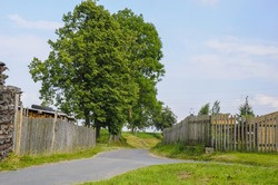A rural lane with fences and trees in Radnavice, the Czech Republic