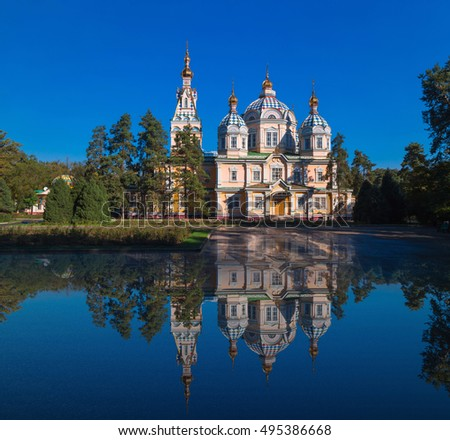 A Russian Orthodox church in the morning. A unique world's highest wooden cathedral. Clear reflection in the water, serene landscape.