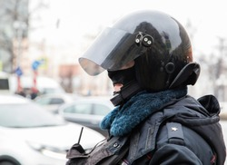 A Russian police major in a protective helmet stands during the opposition protests in Moscow.
