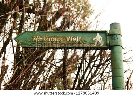 A rusted and flaking green metal sign points left to the