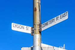 A rusted street sign in Melbourne, Australia on the crossroads of Lygon Street and Cemetery Road East