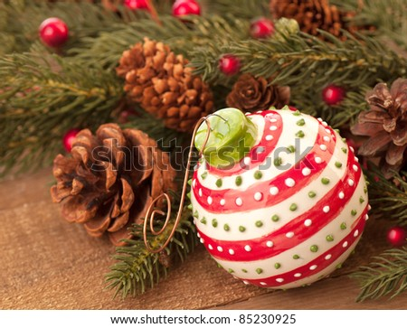 A Rustic and Pretty Christmas Ornament Vignette on Wood and with Pine Boughs, Pine Cones and Red Berries with Room for Text