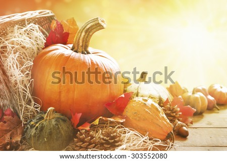 A rustic autumn still life with pumpkins and golden leaves on a wooden surface. Bright sunlight coming in from behind.