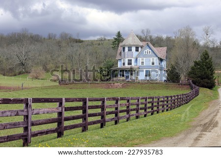 A rustic fence and dirt road by an old Victorian home under an overcast sky in the early spring.   #227935783