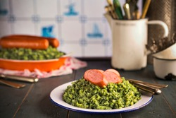 A rustic kitchen with a plate with 'Boerenkool met worst' or kale with smoked sausage, a traditional Dutch meal. Served with gravy. With typical Dutch Delft blue tiles on the wall in the background.