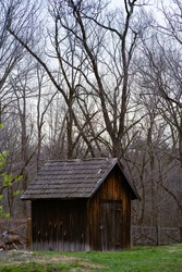 A rustic looking shed is found in the backyard of a house out in the middle of the woods.