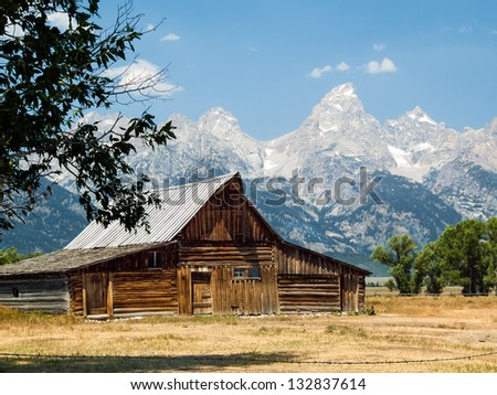 A rustic old barn on Mormon Row in the Antelope Flats area of Grand  Teton National Park, Wyoming with the peaks of the Cathedral Group against a blue sky