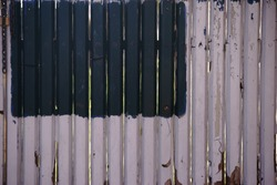 A rustic picket fence with peeling paint and paint cut outs.