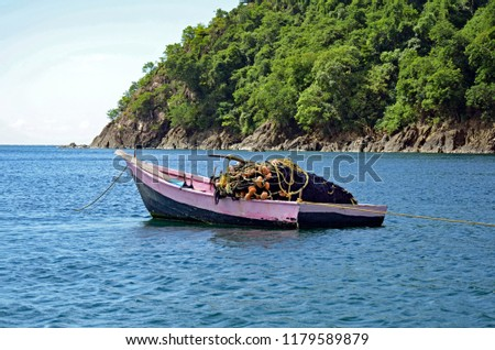 A rustic pink and black fishing boat piled with a seine net with faded orange floats and yellow rope, and a long wooden ore at anchor in a Tobago harbor lined with rugged rocks and lush green plants. #1179589879