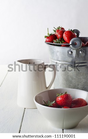 A rustic table scene of freshly harvested strawberries, just harvested.  Includes a tin pail of strawberries, a cream jug and a bowl of served strawberries.
