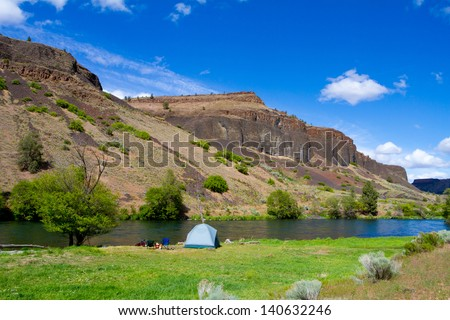 A rustic tent campsite on the Deschutes River in Oregon shows a tent setup next to a boat and the river. This is form a float camping trip.