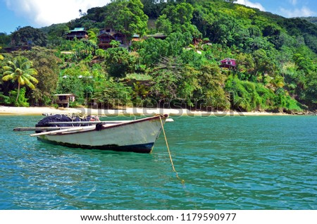A rustic white and black fishing boat storing a seine net with orange floats and yellow rope, and long wooden ores moored off a Tobago beach with lush greenery and colorful houses up the mountainside. #1179590977