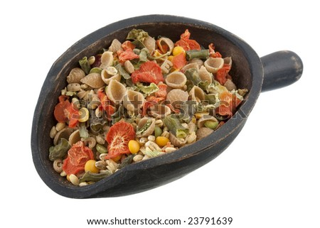 a rustic, wooden scoop of vegetable soup mix including whole wheat pasta, carrots, peas, leeks, green beans, bell peppers, corn, celery and onions, isolated on white