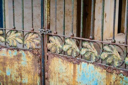 A rusting gate, with a leaf motif, is chained and padlocked against entry.