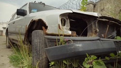 A rusty abandoned car in the parking lot, surrounded by a fence and barbed wire. A couple of cars are standing in a sump for automotive disassembly or metal processing. Restoration of a retro car.