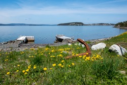 A rusty anchor lays among green grass and yellow flowers. There are two wooden piers in the distance surrounded by calm blue water, blue sky, and clouds with mountains and land surrounding a cove.