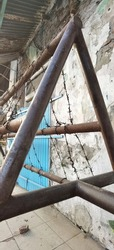 A rusty barbed wire barricade on the street in front of abandoned house
