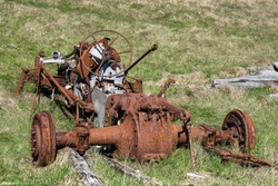 A rusty car wreck with engine block, differential and axles at its final resting place in a field