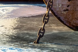 A rusty chain of an old anchor frozen into the ice.