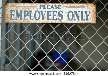 A Rusty 'Employees Only' Sign on a Chain Link Fence at an Abandoned Industrial Building