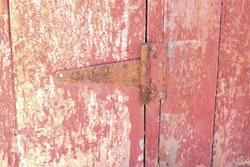 A rusty metal hinge is on the outside of a barn door.
