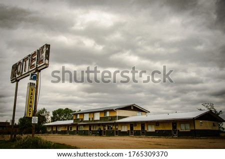 A rusty metal motel sign with wooden old motels under the cloudy and rainy  sky Сток-фото ©