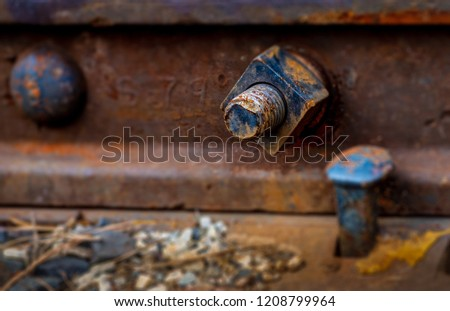 A rusty nut and bolt protrude through a railroad track.  There is a railroad spike, track and gravel visible