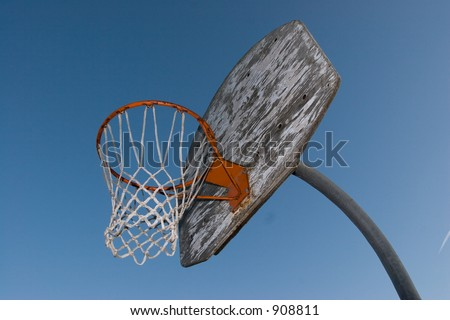 A rusty old basketball hoop against a blue sky in the evening.