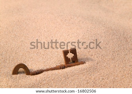 A rusty old key part buried in sand.