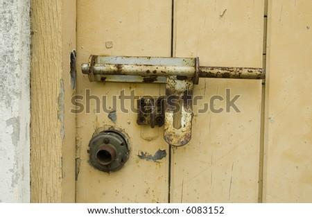 a Rusty Padlock on a yellow wooden door