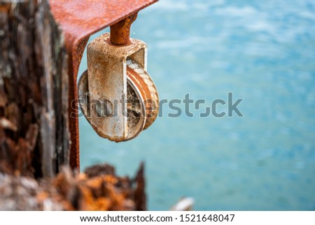A rusty roller with an arm from an old winch or hoist for pulling and unloading cargo or fish from fishing ships and boats to a wooden pier #1521648047